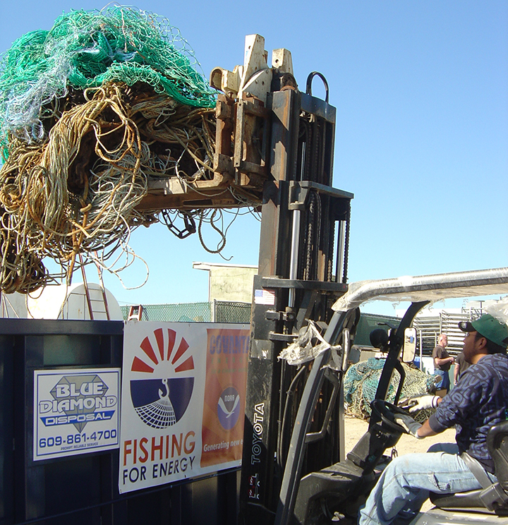 Man using a forklift to place old fishing nets in a collection dumpster.