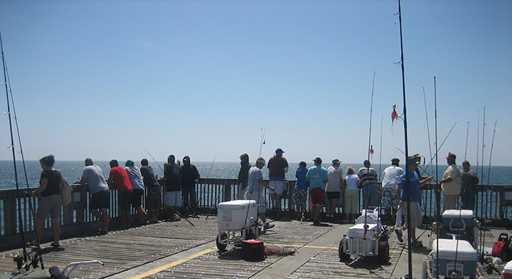 People standing around a pier fishing.