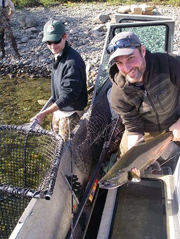 A NOAA scientist takes stock of a male Chinook salmon during their fall run along the Hanford Reach in 2013.