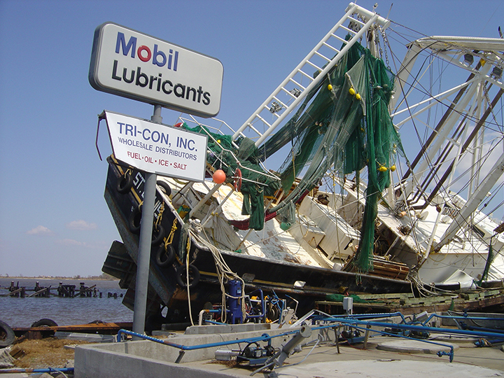 A damaged boat setting on a  fuel dock.