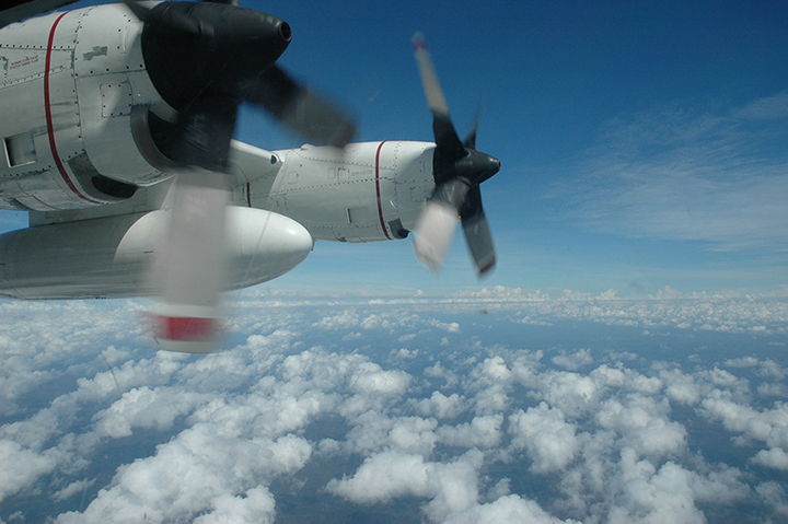 Looking out of an observer window on a Coast Guard C-130 airplane over the ocean.