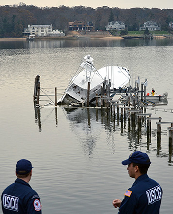 Coast Guard responders oversee a partially submerged vessel in Navesink River, N.J., Nov. 10, 2012. Boom was placed around the vessel to mitigate pollution during the response efforts.
