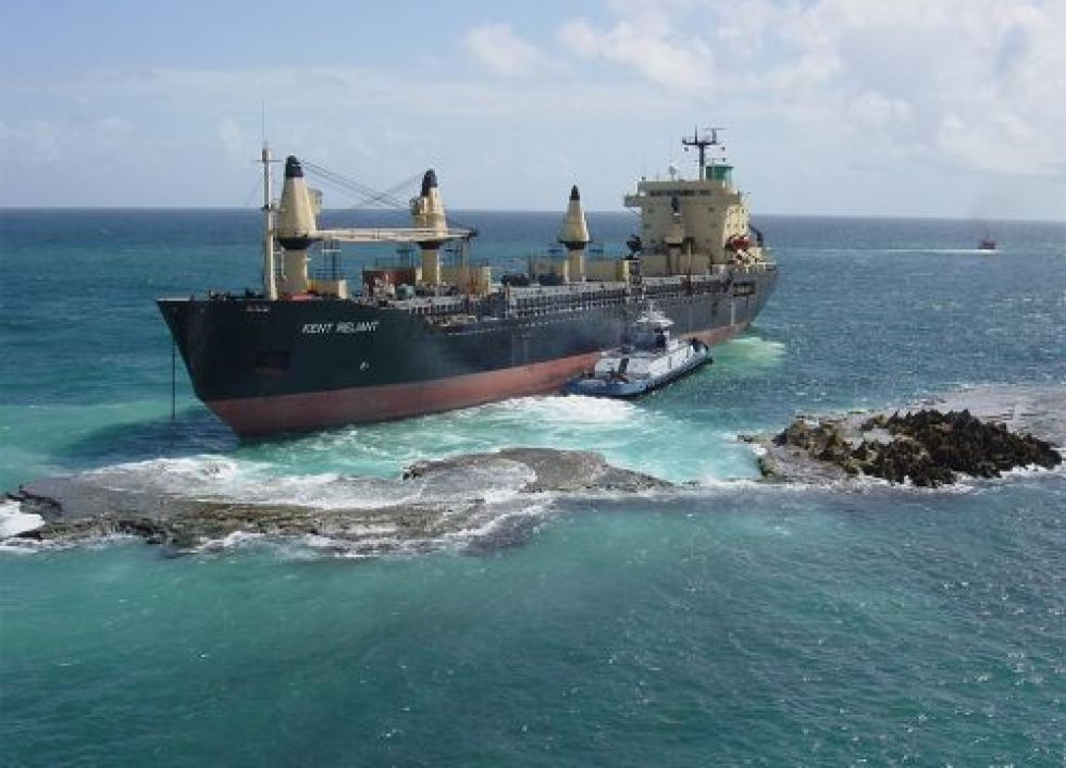 Large ship on reef with small boat beside it.