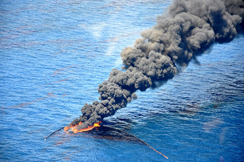 Ocean with black smoke from burning oil.