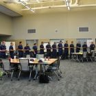 Students from the U.S. Coast Guard stand in a line around a conference room.