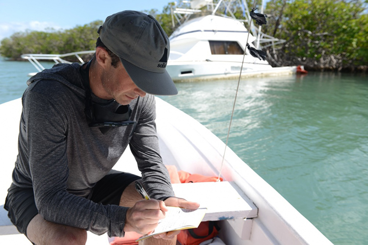 Man making written notes while sitting in a boat near a capsized boat.