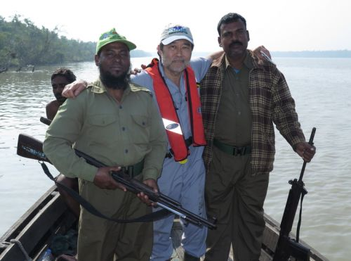 A man posing with two men holding guns on a boat.