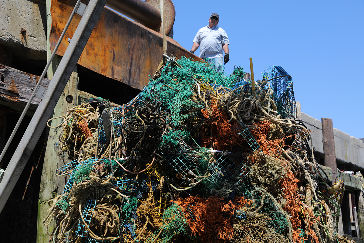 A large ball of marine fishing nets being pulled up to a dock.