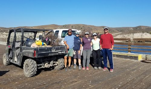 A group of people on a boardwalk posing for a photo next to a vehicle with a pile of marine debris in the truck bed.
