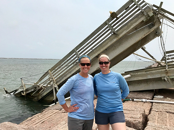 Two women standing in front of a collapsed structure.