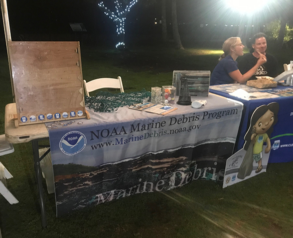 "A table with a ""Marine Debris Program"" poster and a plinko board."