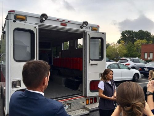 A person in front of an ambulance talking to a group of people.