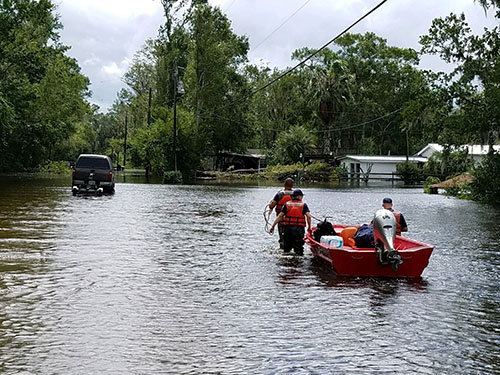 Three people wearing life jackets guide a boat as they wade through flood waters.