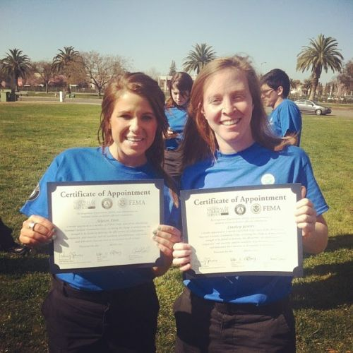 """Two people holding """"Certificates of Appointment"""" with a FEMA logo on it."""