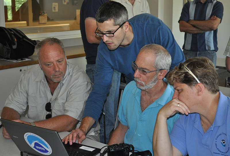 Person instructing three others at a computer screen.