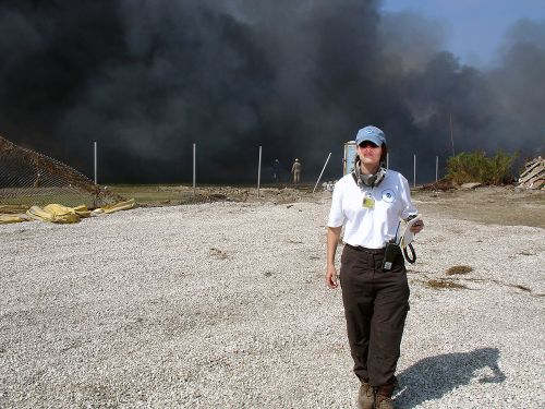 A woman walking toward the camera with smoke billowing behind her.
