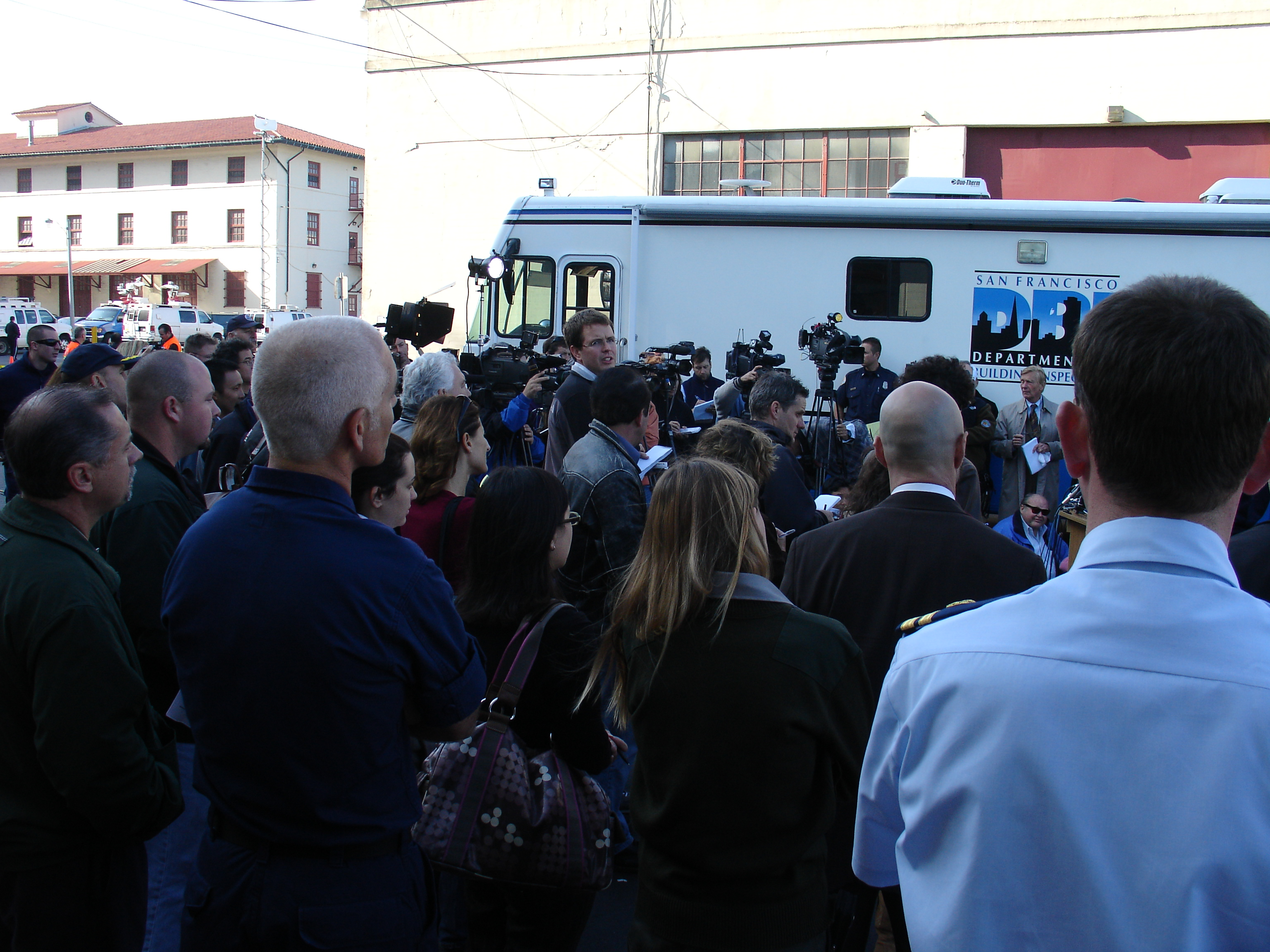 A group of people and press gather around a media vehicle.