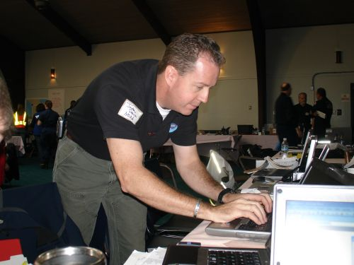 A man leaning over a laptop typing.