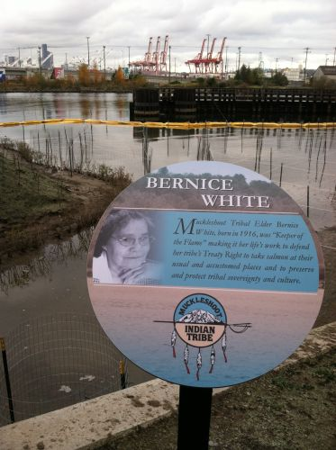 "A sign with the name ""Bernice White"" and a picture of a woman in front of a shoreline."