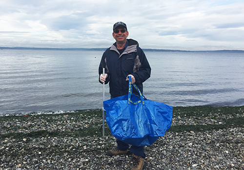 Man with large blue bag standing on a beach.