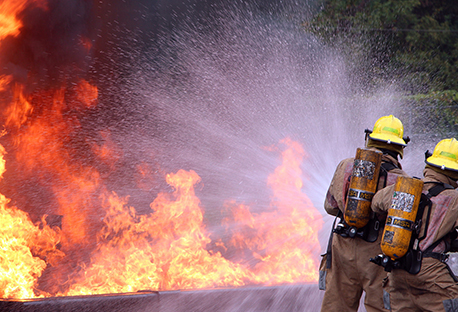 Two firefighters spraying water onto a fire.