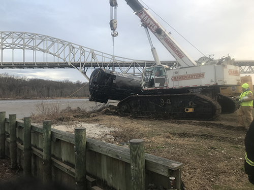 A crane towing a rail car from the river.