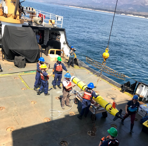 People working with an AUV on the deck of a vessel.
