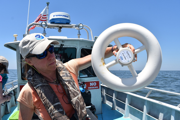 Woman holding up a large white plastic ring in a boat.