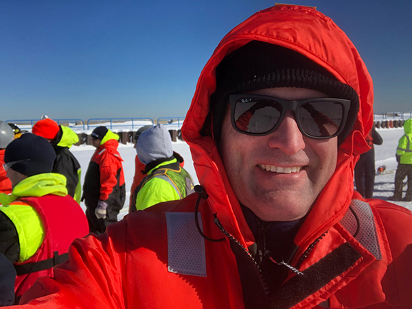 Man in a red coat smiling at camera.
