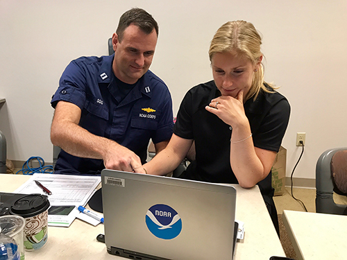 Two people working at a laptop.