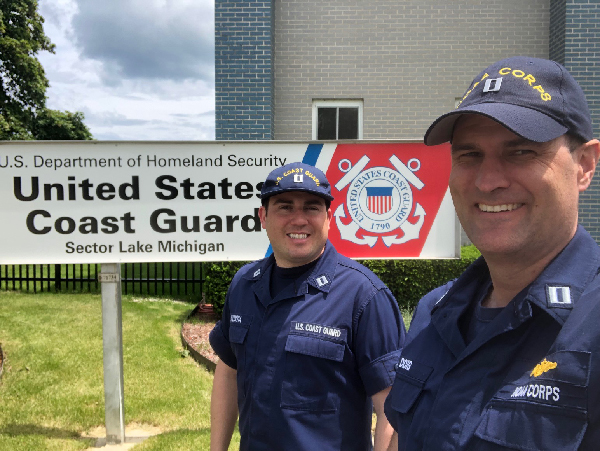 Two men looking into camera, USCG sign in background.