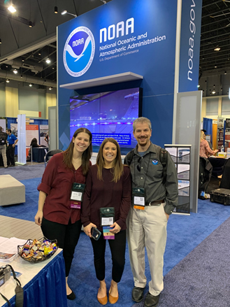 Three people in front of a NOAA logo.