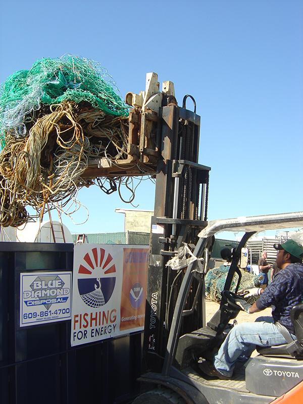 Forklift truck loading nets into a disposal bin.