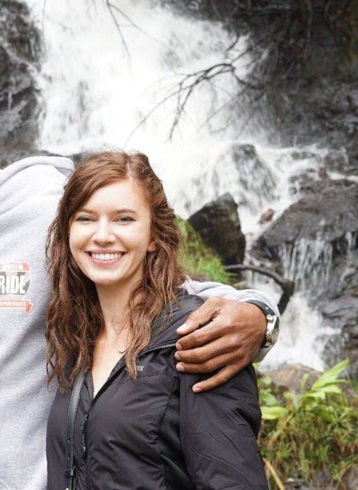 Woman in front of waterfall with someone's hand resting on her shoulder.