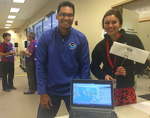 "A man and a woman stand behind an open laptop on a table while they pose for a photo. The woman is holding a small sign that says ""GIS."""