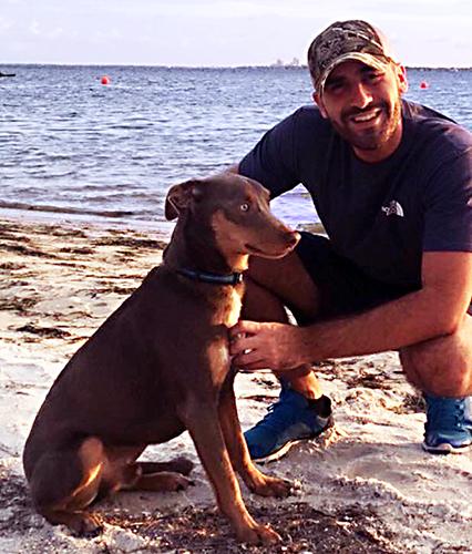 A man and a dog on the beach.
