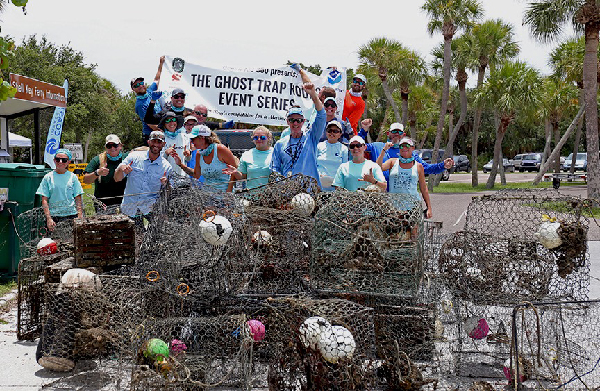 People posing with crab pots and debris.