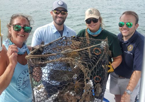 Four people posing with crab pot and debris.