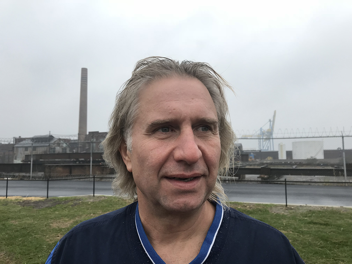 A profile shot of a man with an industrial setting in the background.