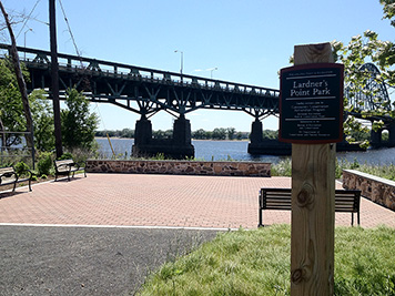 Park next to a river; bridge in background.