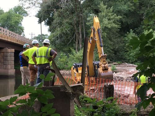 Workers and heavy equipment at a river work site.
