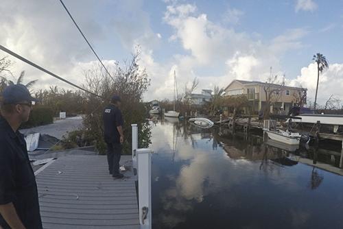 Two men standing on dock next to debris-filled waterway.