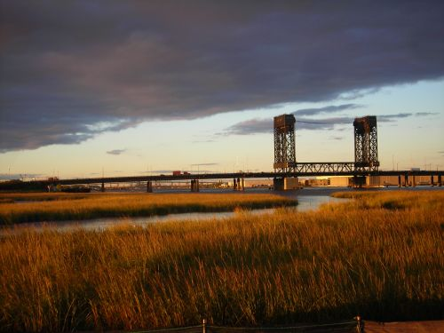 River running through a marsh; bridge in background.