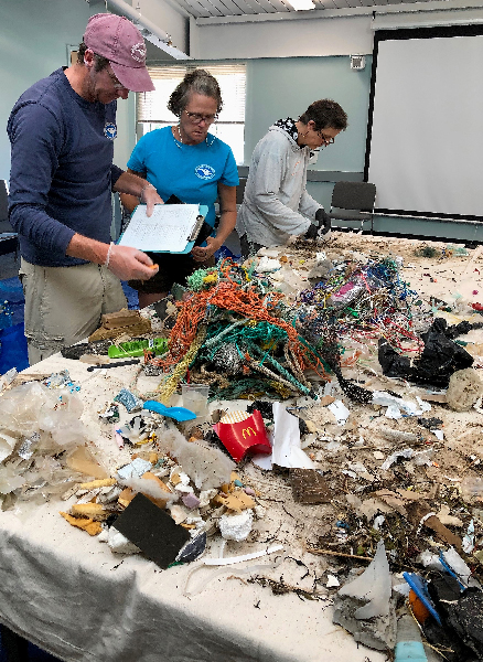 Three people working at a table covered in trash.