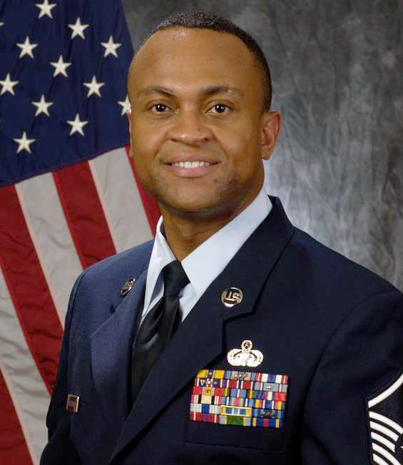 A man in a military uniform in front of a U.S. flag.