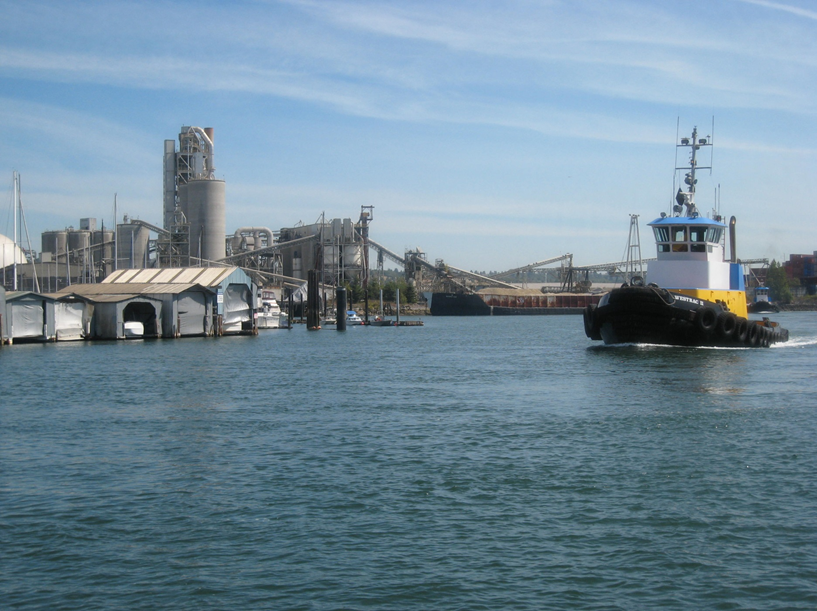 A boat navigating down a river with an industrial shoreline in the background.