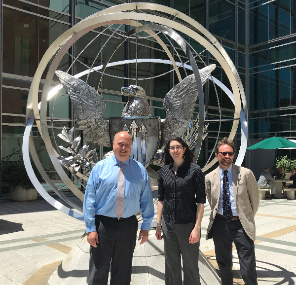 Three people pose in front of the Interagency Modeling and Atmospheric Assessment Center.