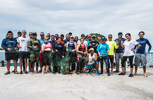 large group of people pose for photo on a beach.