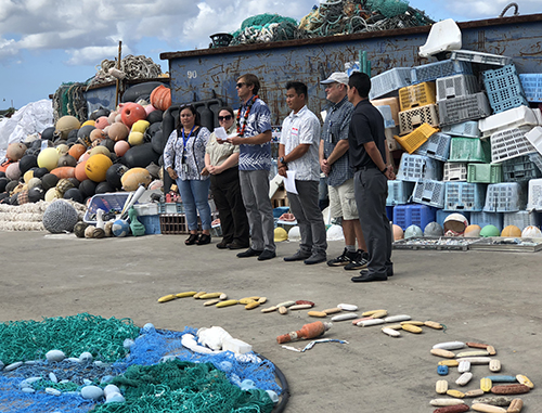 Speakers address a group with marine debris display.