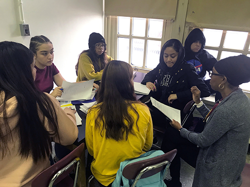Group of students sitting at a table, working together.